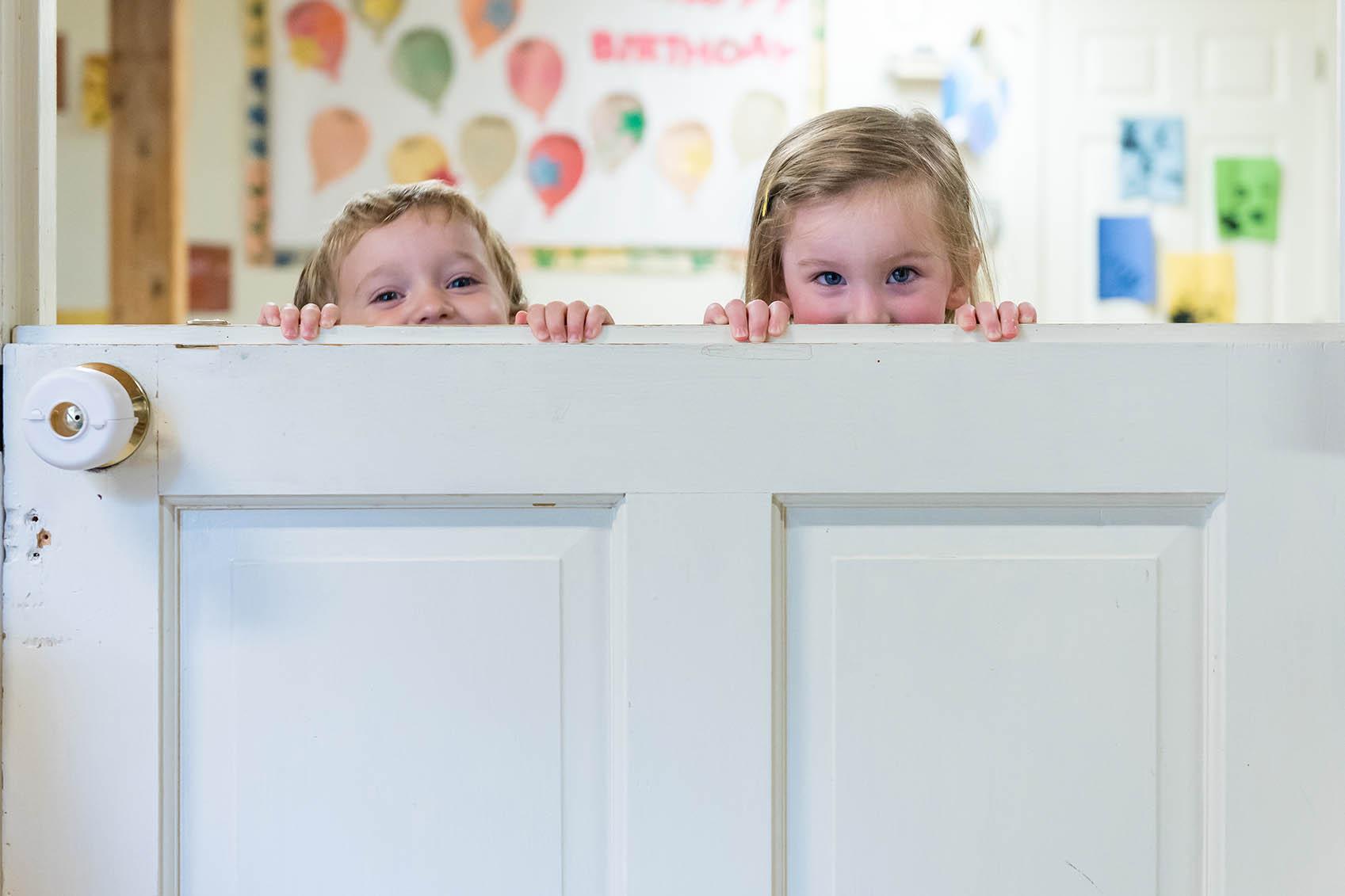 Young children peeking over door