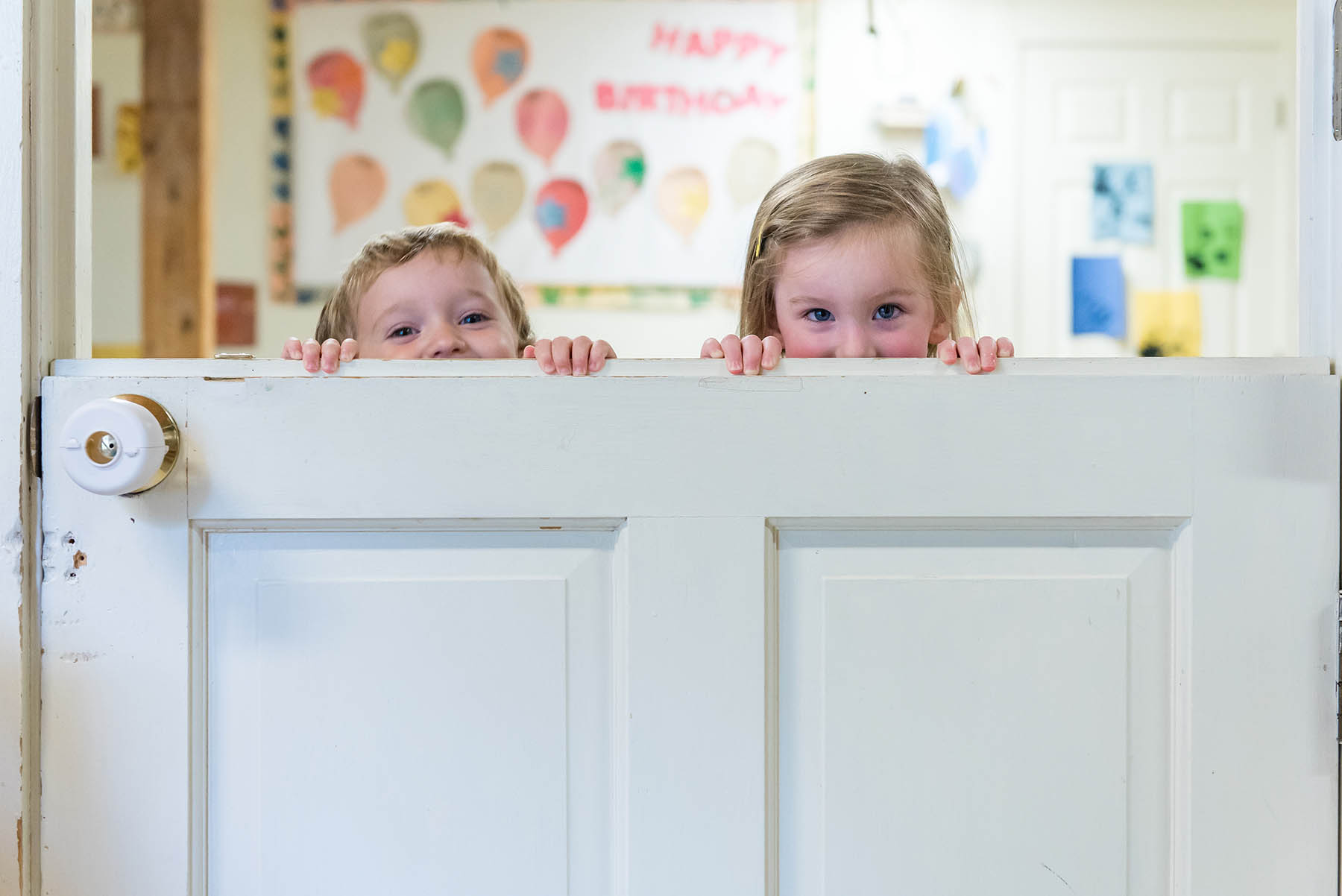 Toddlers peeking over door