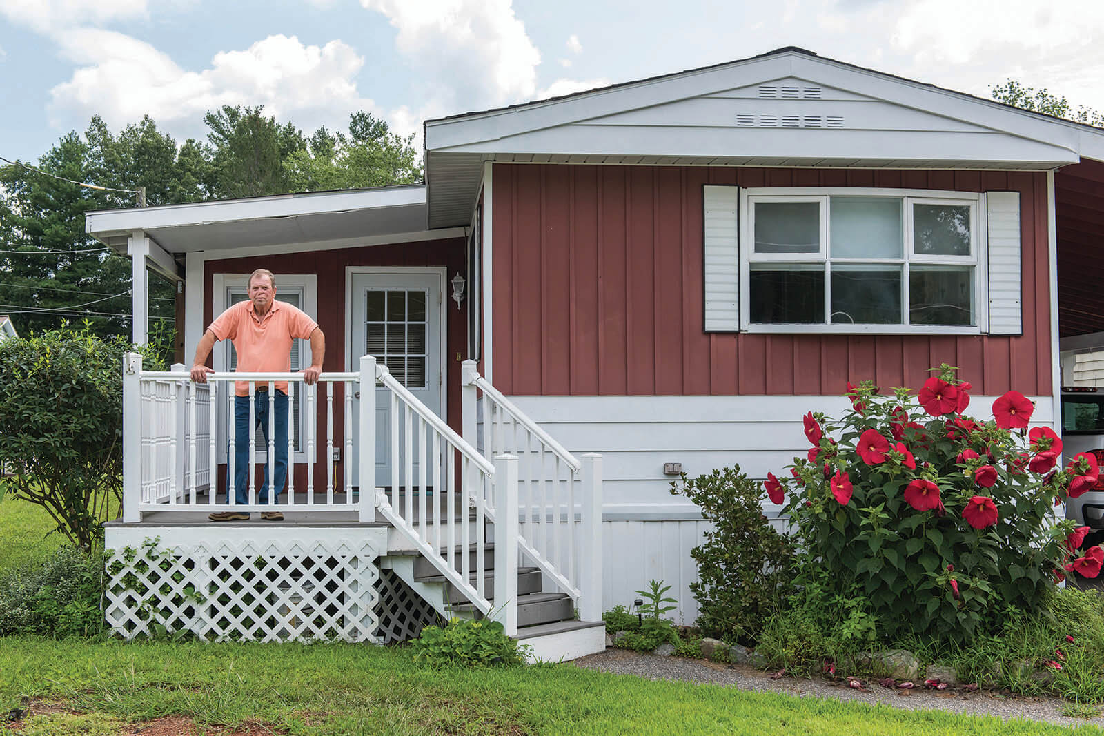 Man standing on porch of manufactured home