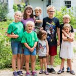 Preschool teacher and students stand outside the school