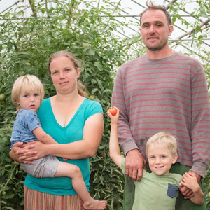 Farm family of four poses in greenhouse