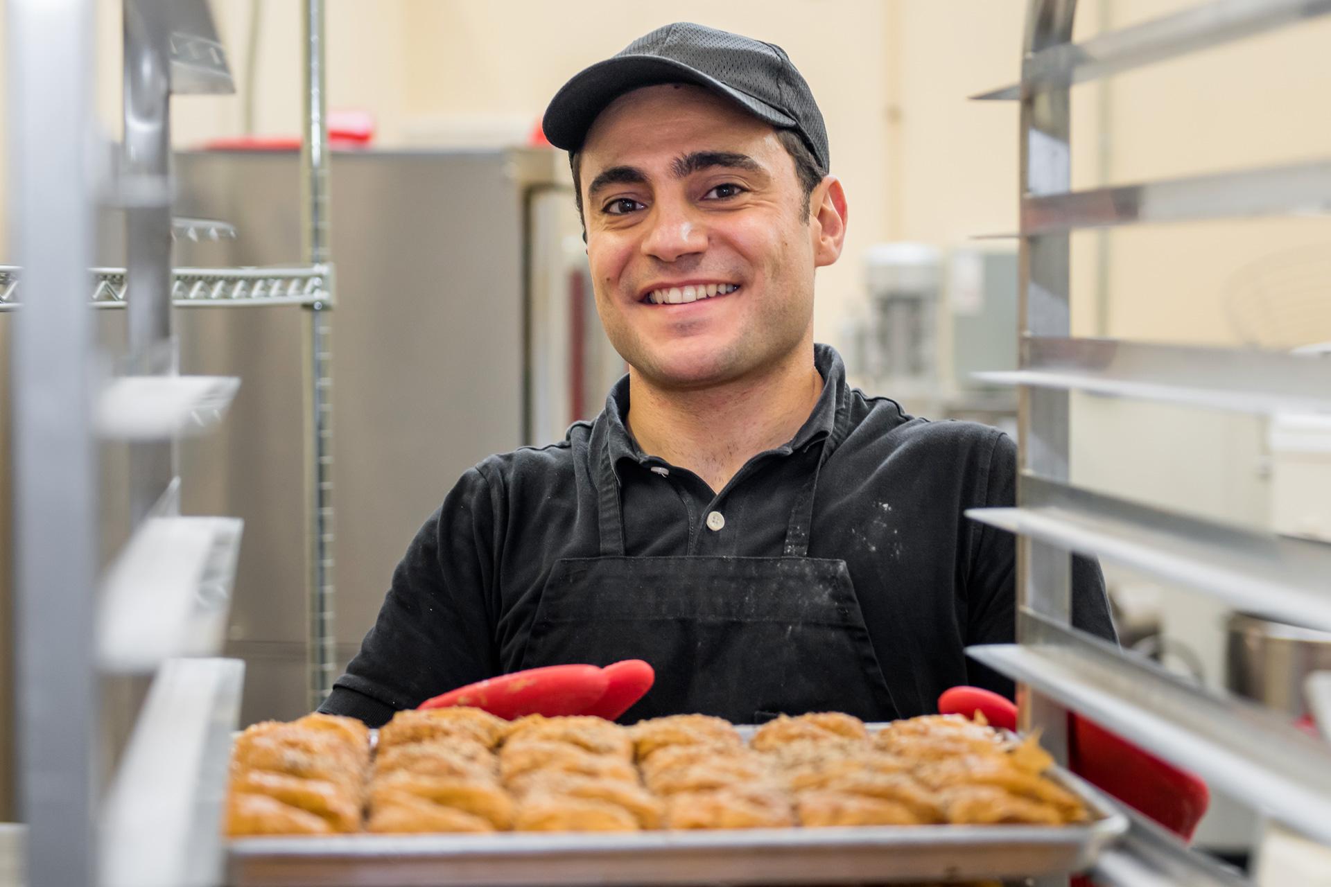 Smiling man loads a tray of baklava