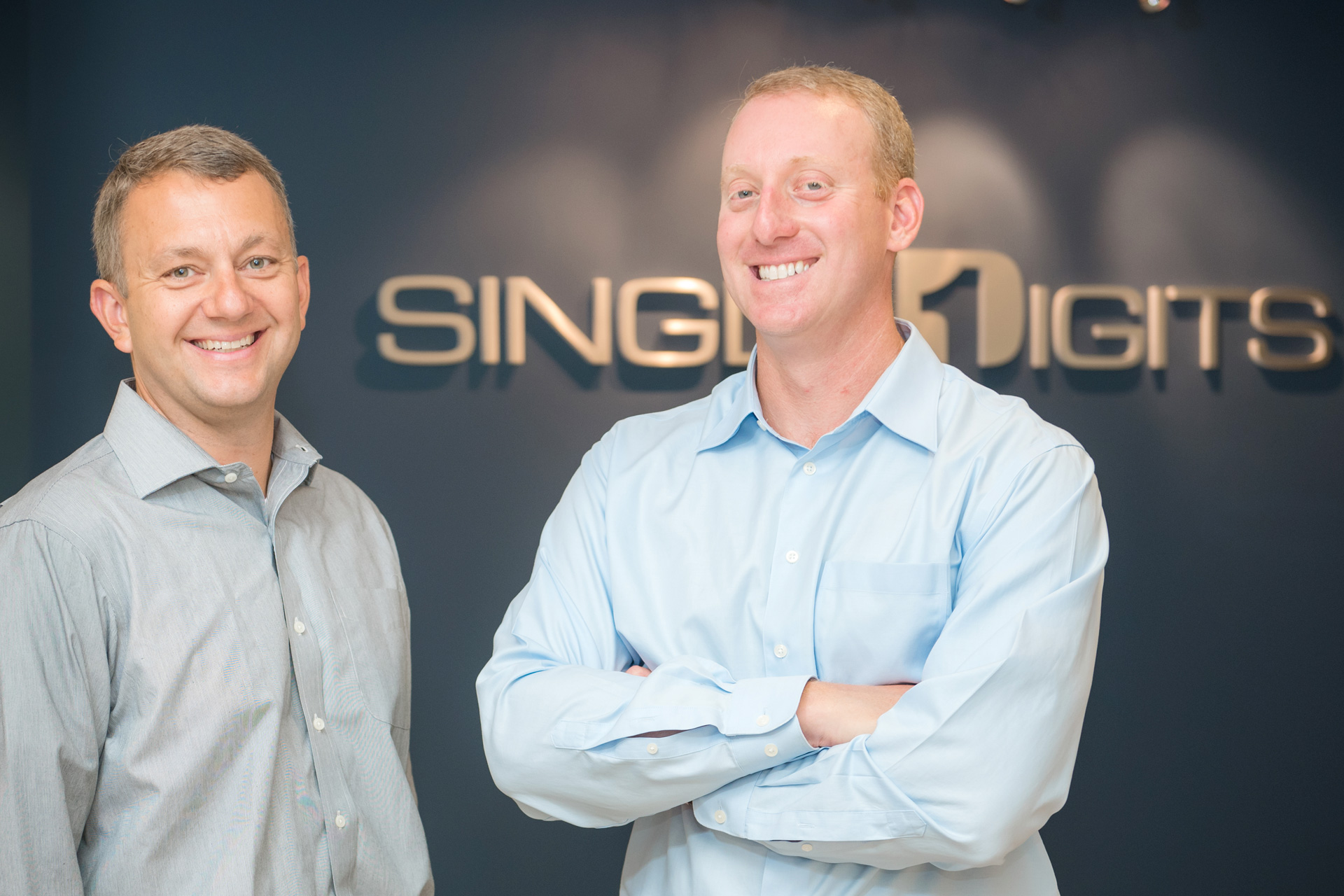 Two men stand in front of the Single Digits logomounted on the wall