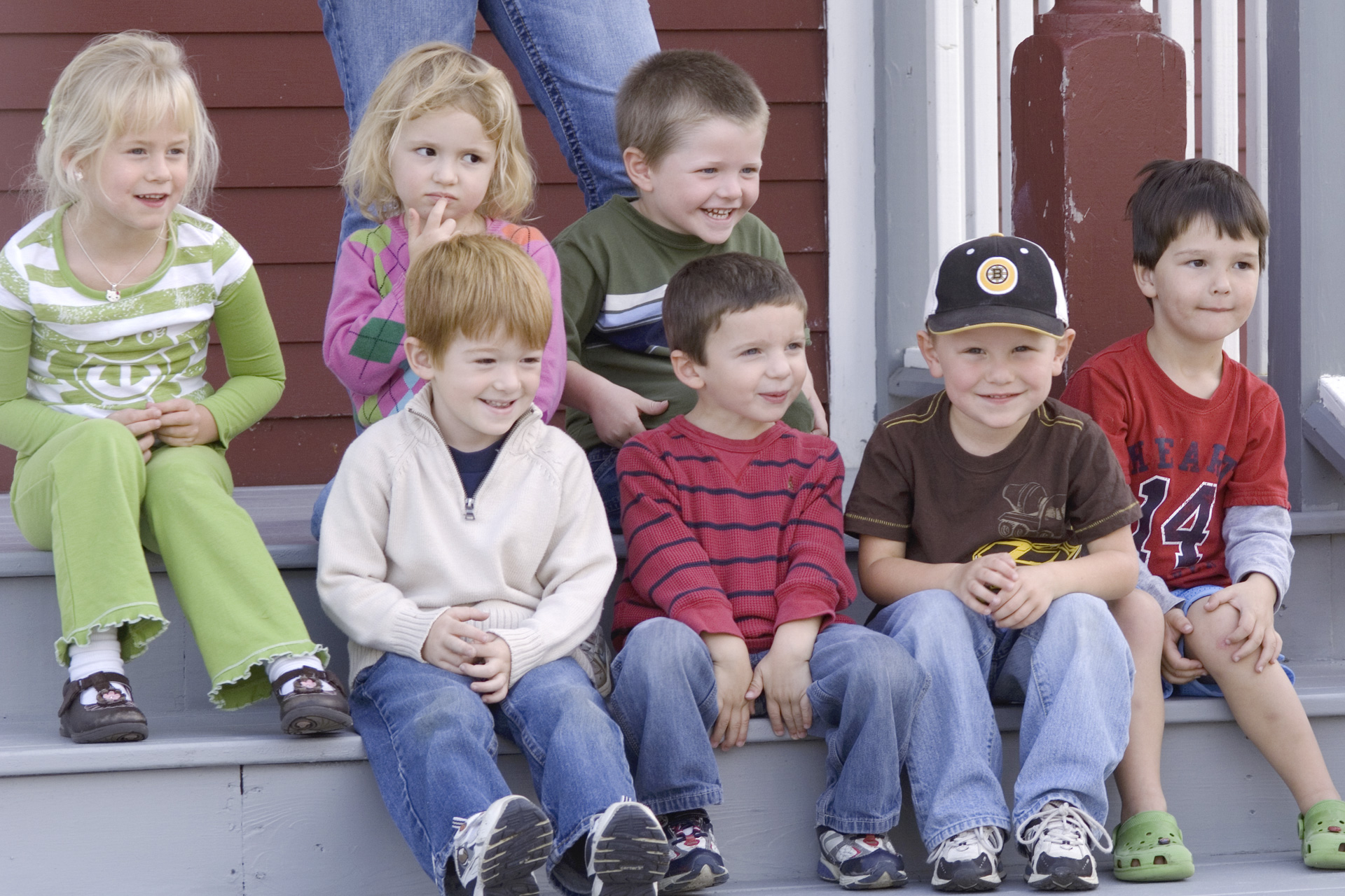 A small group of children sit on the stairs of their school