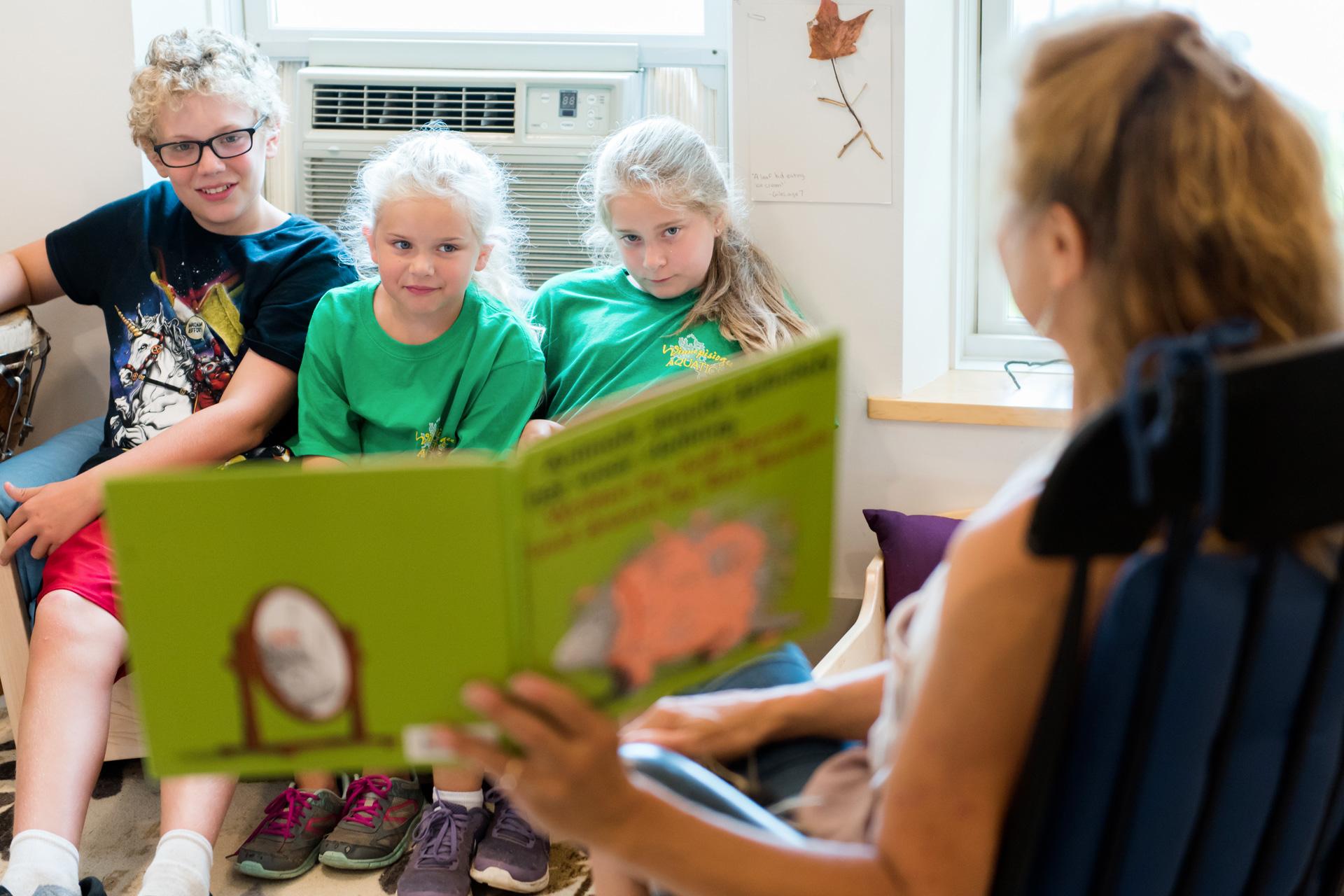 Teacher reads to three rapt students