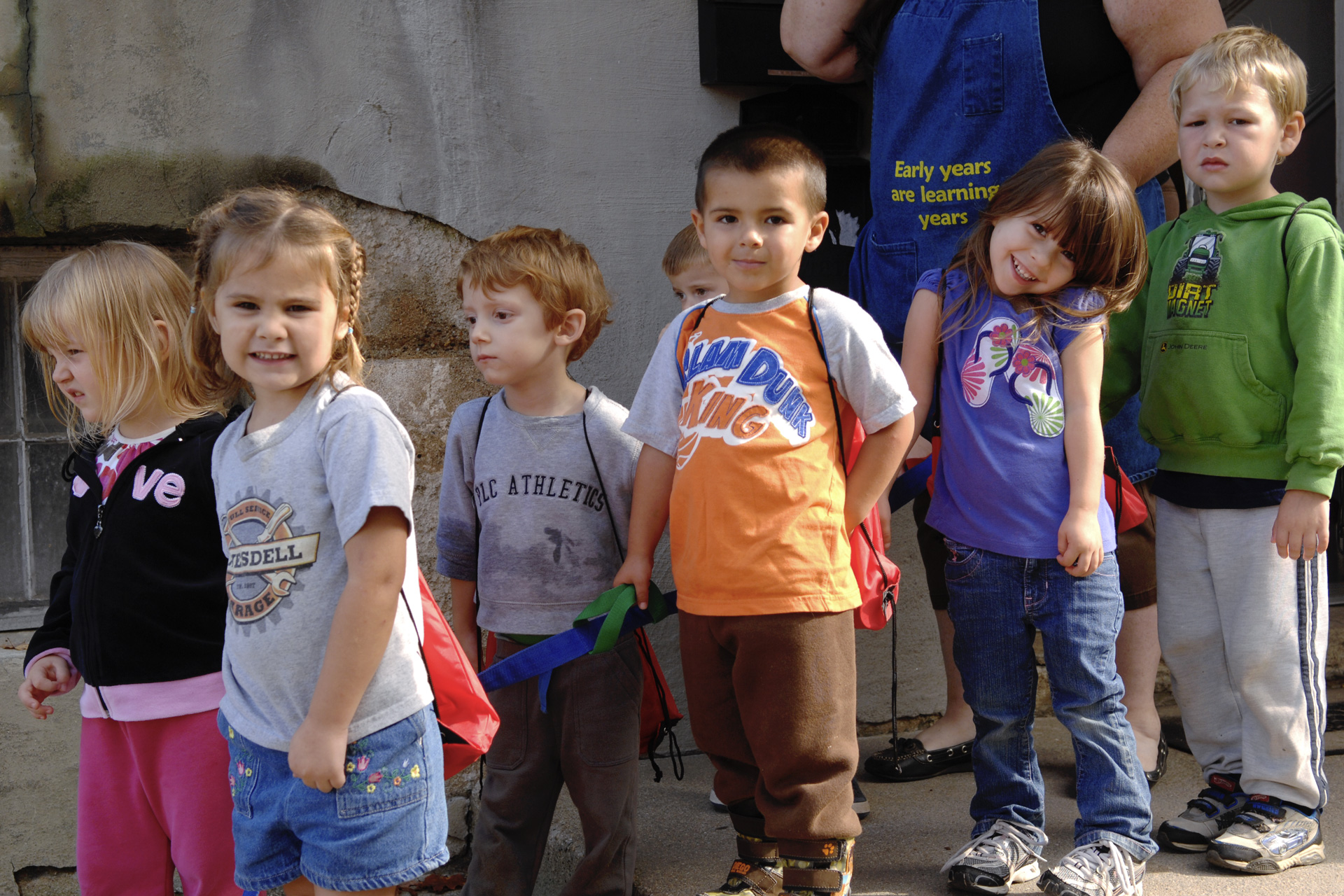 A group of toddlers waits in line