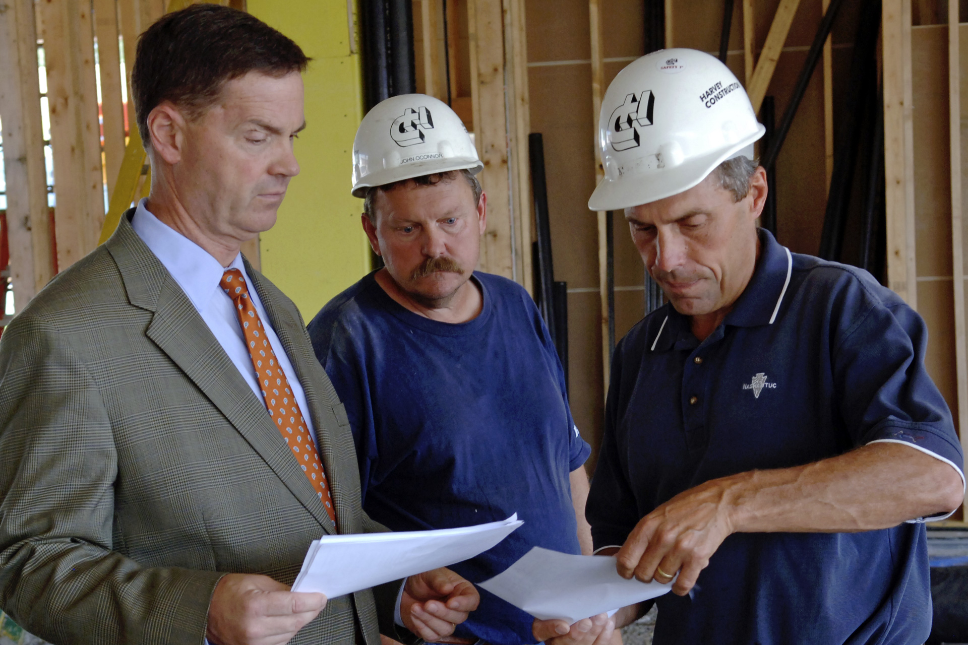 Man in suit and tie talks with a couple builders in safety helmets