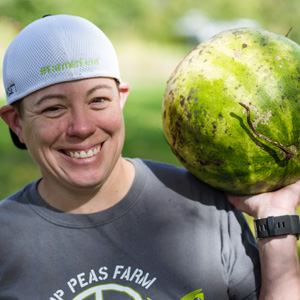 Worker with a Hip Peas Farm tee shirt carrying a watermelon