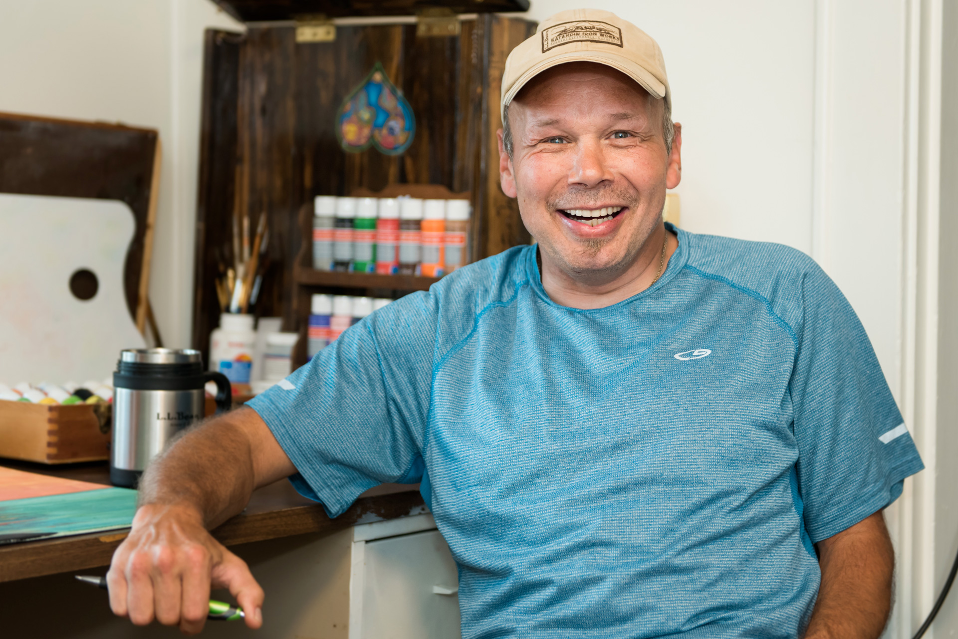 Man in cap leans on a desk, a set of paints behind him