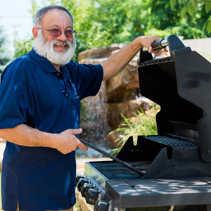 Man cooking on outdoor gas grille