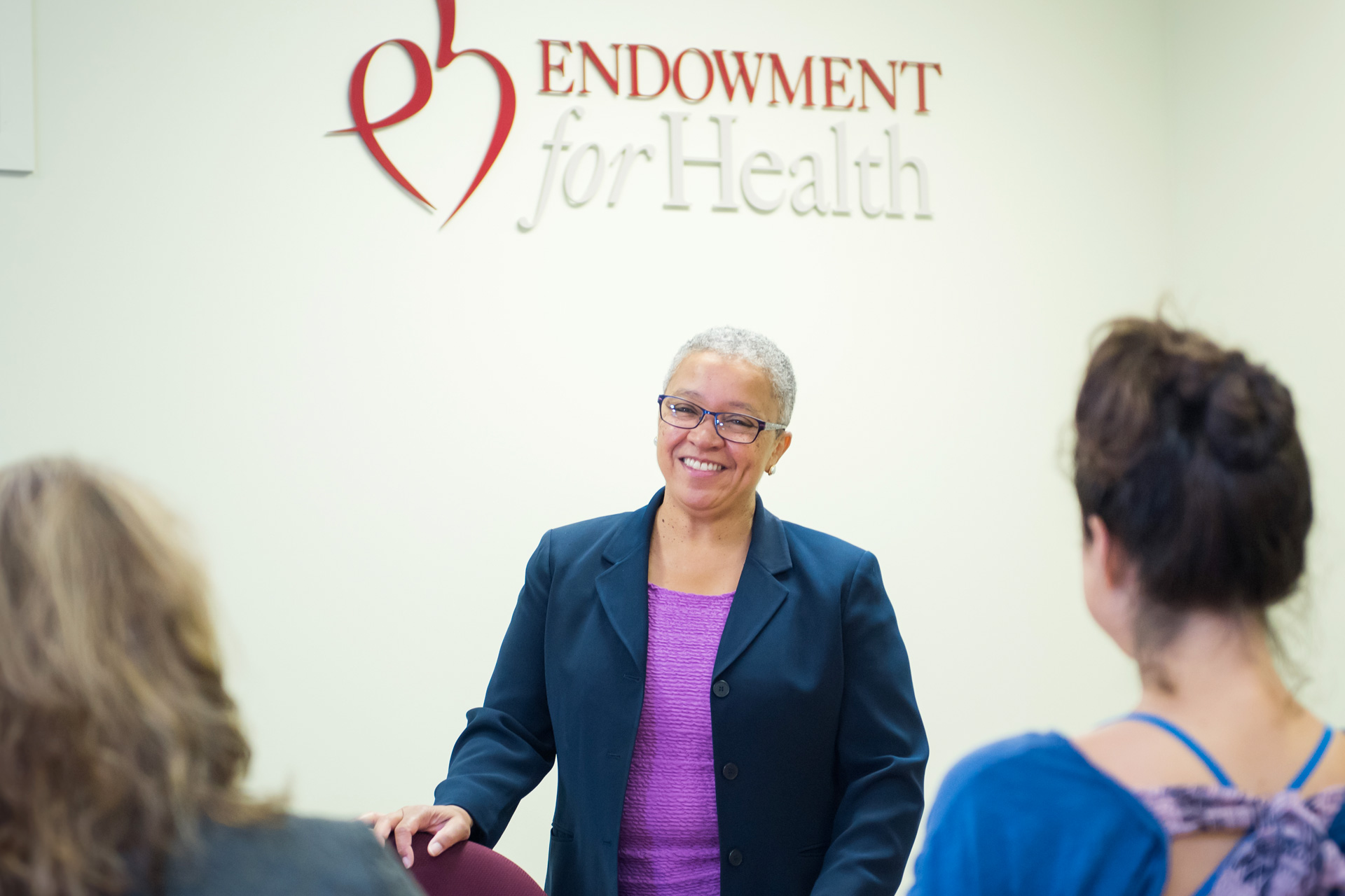 Woman speaks to visitors with Endowment for Health logo behind her