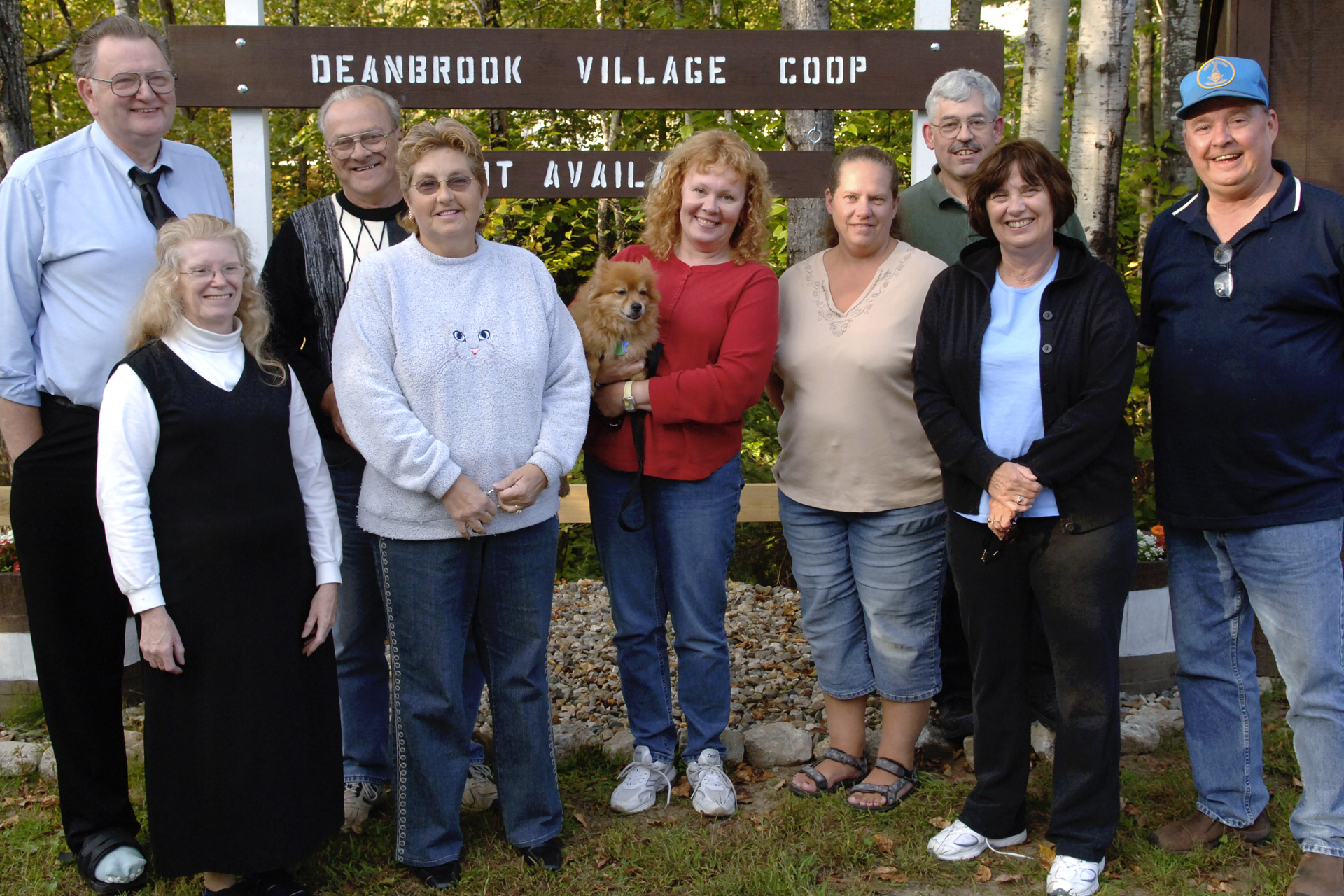 A group of adults stand in front of a sign that reads Deanbrook Village Coop