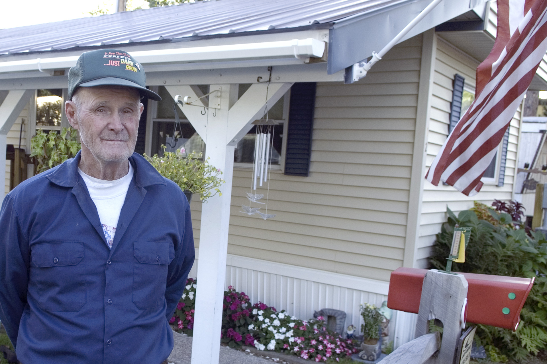 Man stands with manufactured home in background