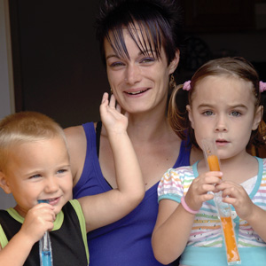 A young mom with her son and daughter, eating popsicles