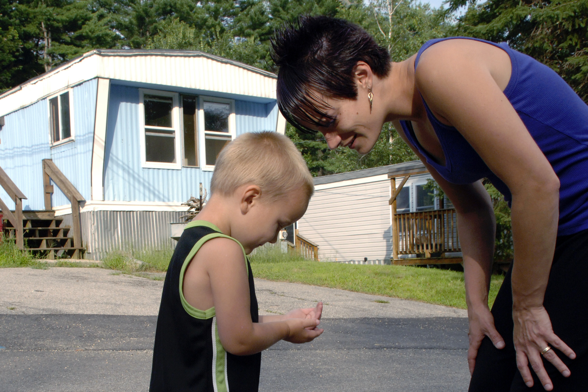 Young boy stands on road and shows his mother a discovery