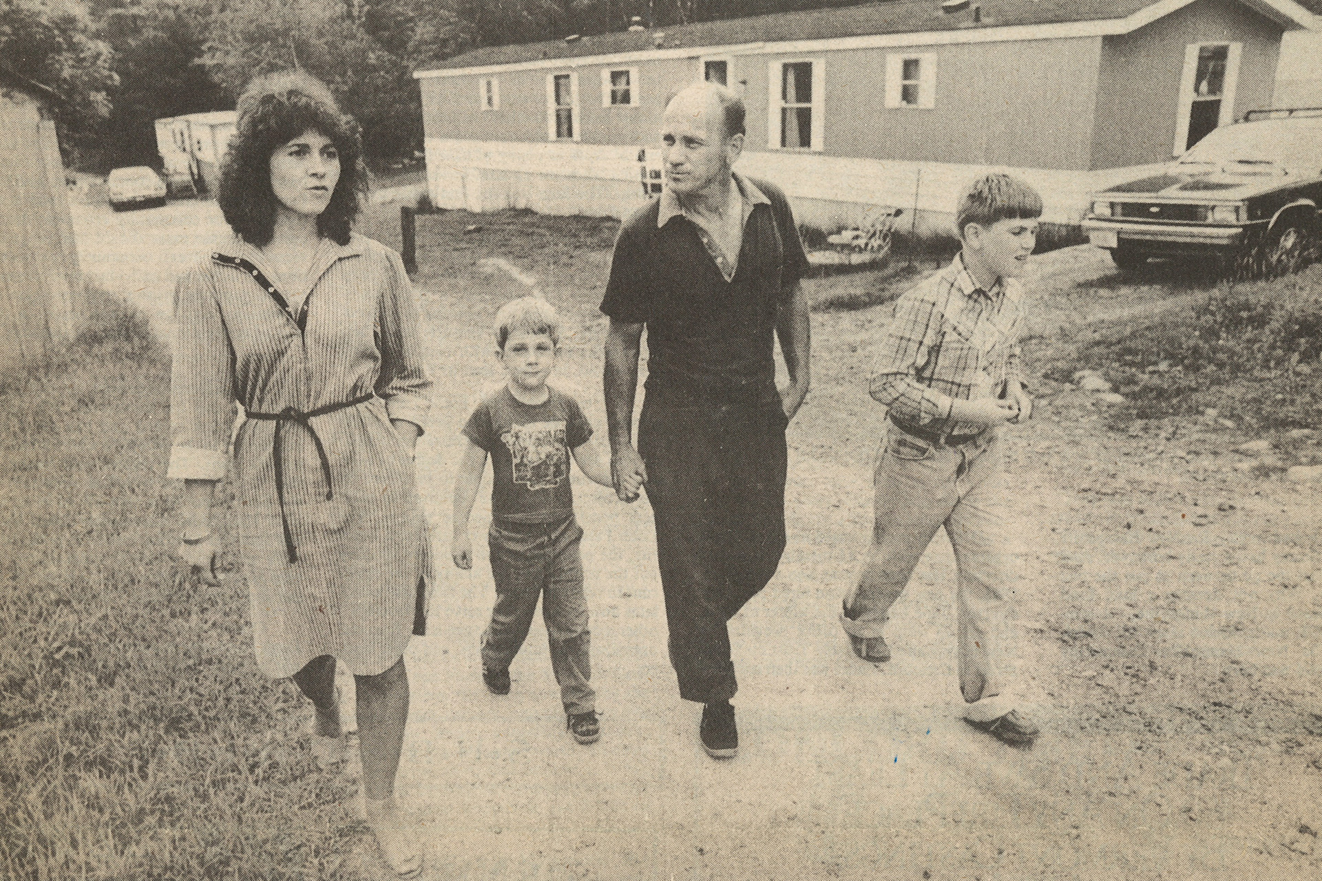 Black and white newspaper photo of a woman walking on gravel street with a man and two young boys