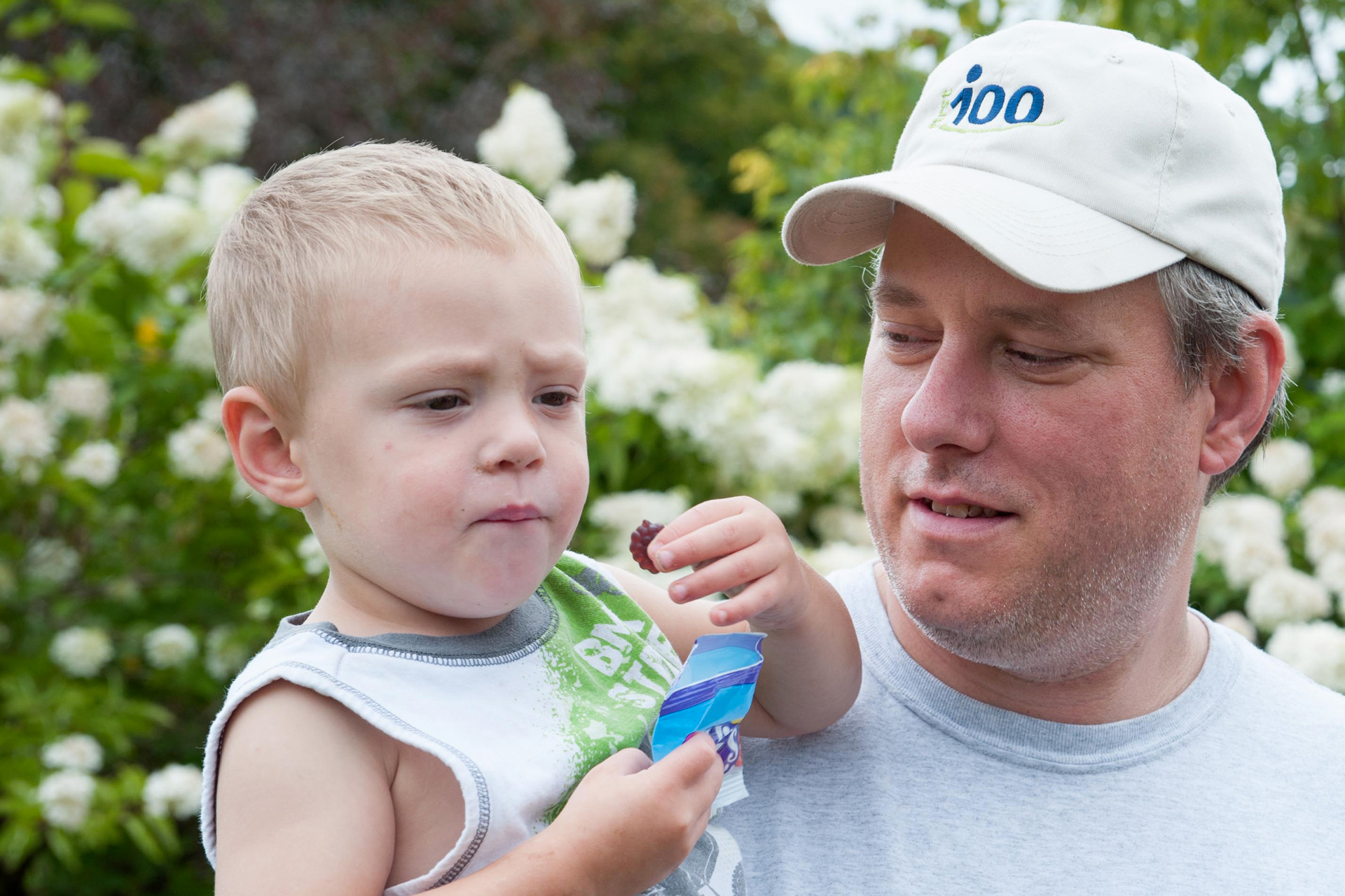 Man holds his young son, who is having a snack