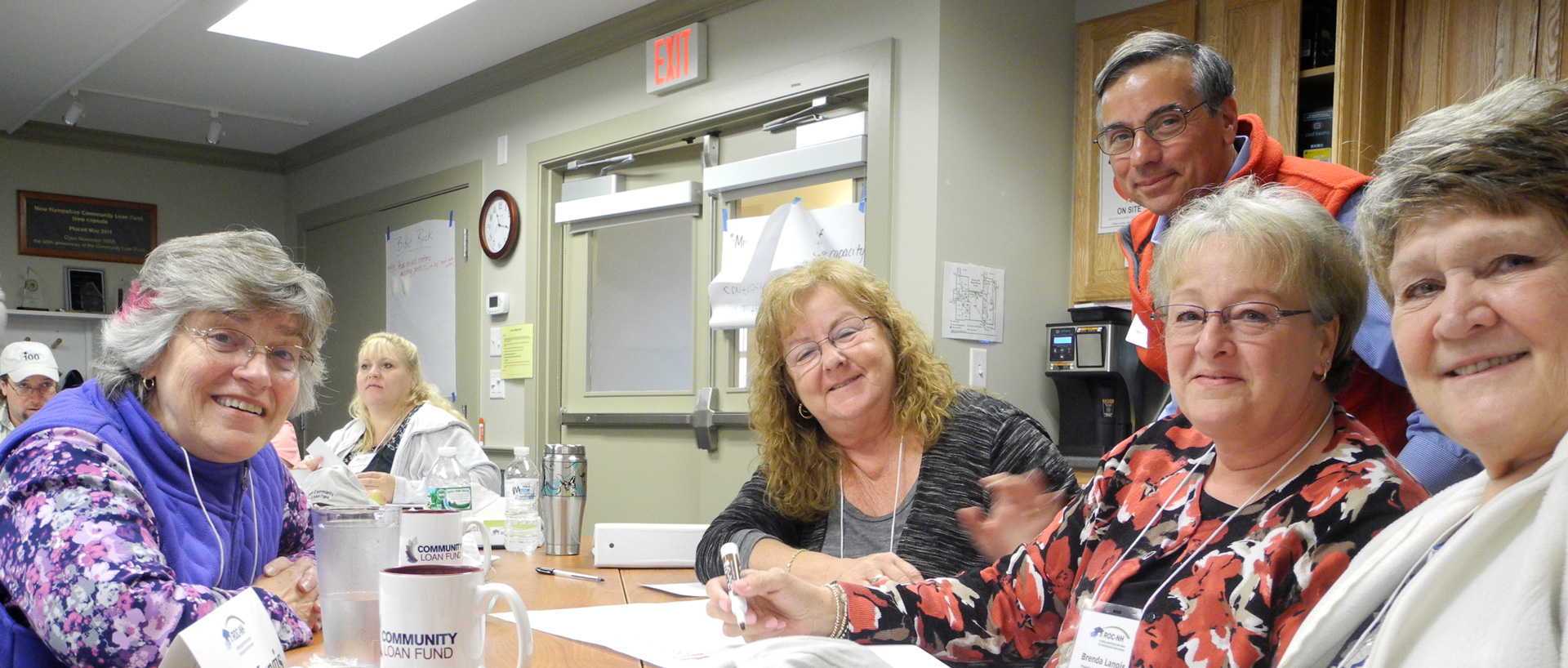 group working around table and smiling at camera