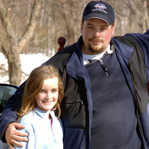 Man with hand on his daughter's shoulder