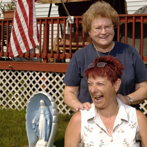 Two woman stand on the lawn outside a manufactured home