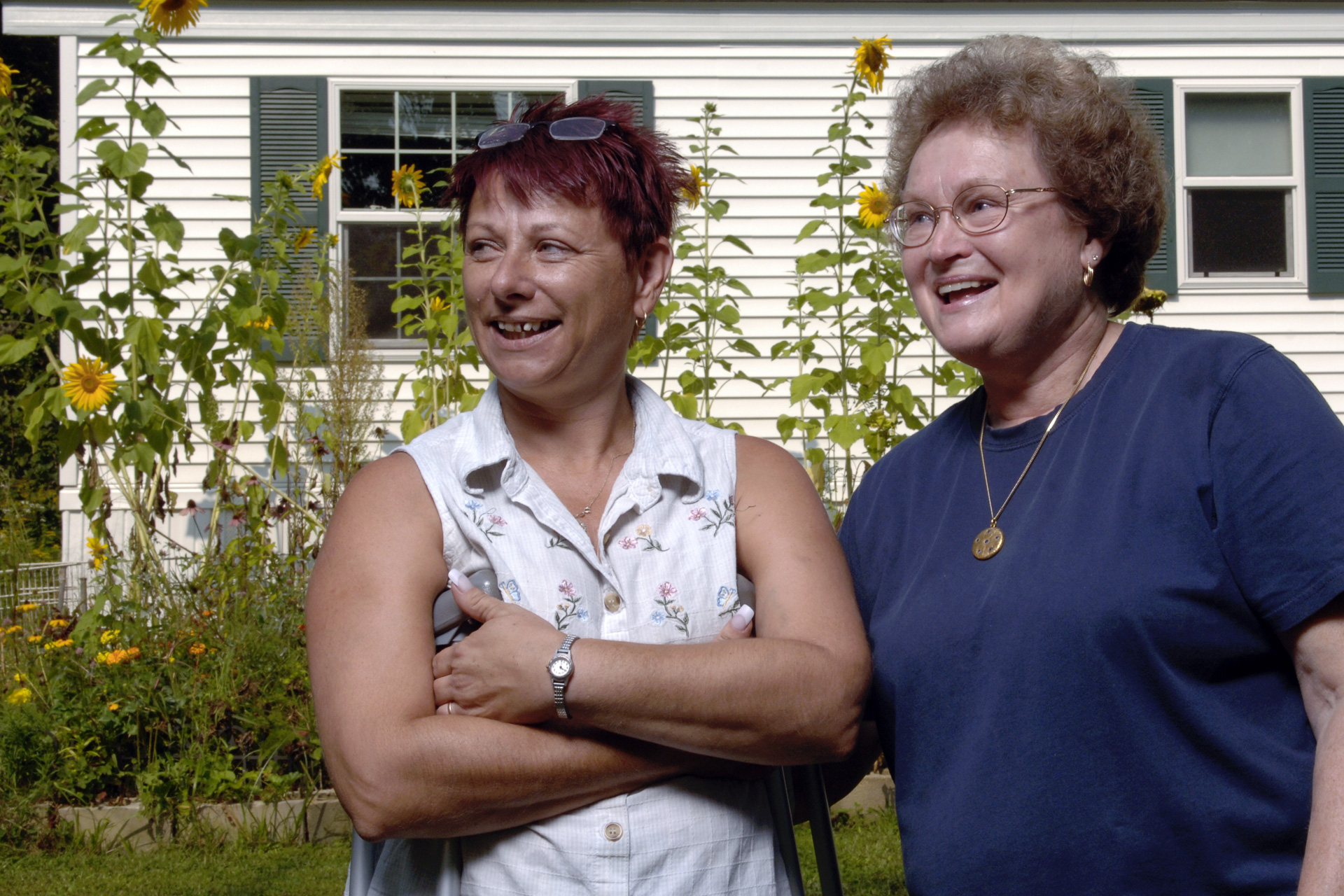 Two women stand on lawn outside manufactured home