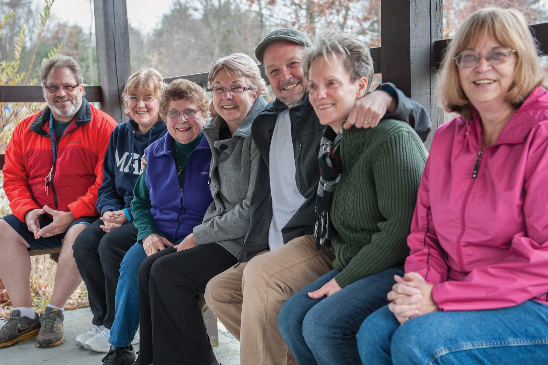 A line of smiling adults, seated