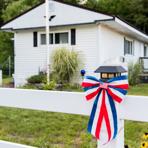 Red, white, and blue ribbon tied to a post in front of a new manufactured home