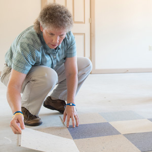 Woman setting down floor tile