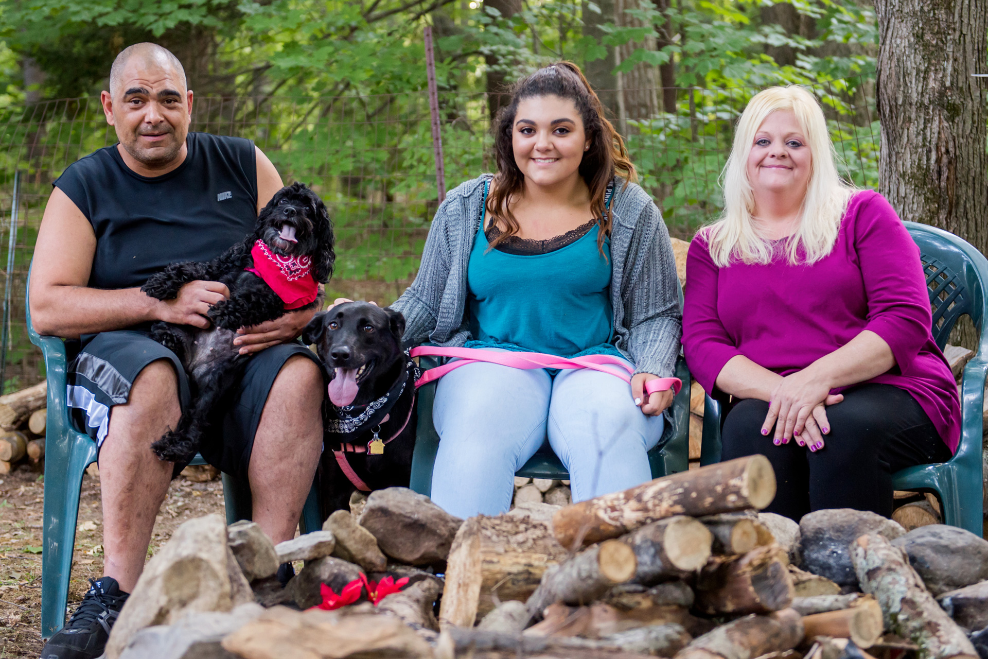 A dad, mom, daughter, and two dogs sit outdoors by the wood pile
