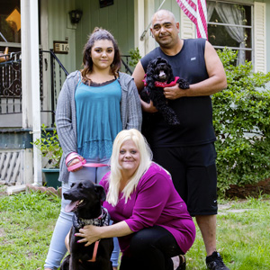 A dad, mom, daughter, and two dogs sit stand outside their manufactured home