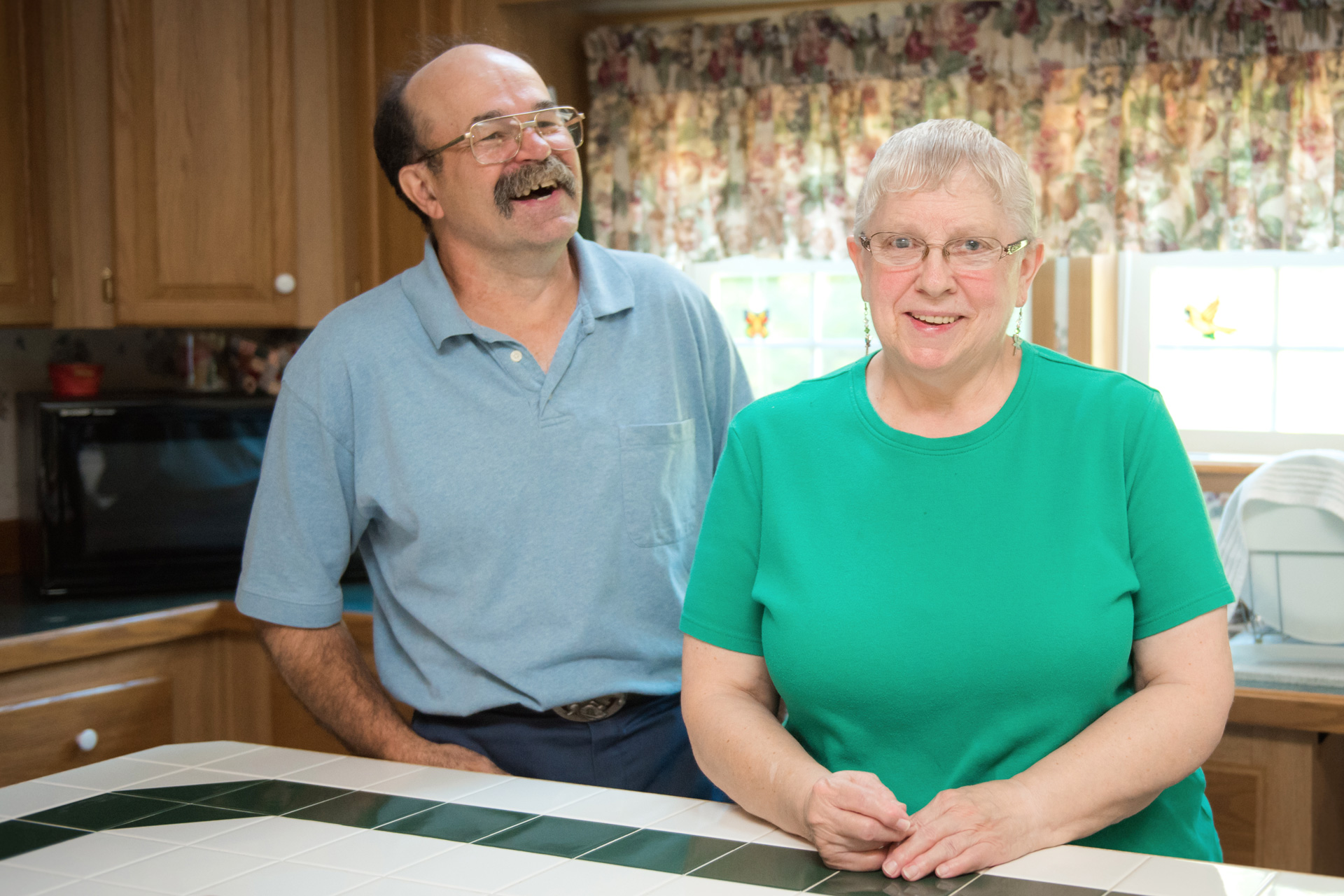 Man and woman stand at kitchen counter; man is laughing