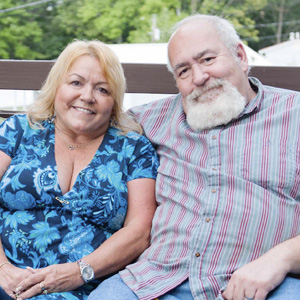 Middle-age couple sit on a loveseat on their deck