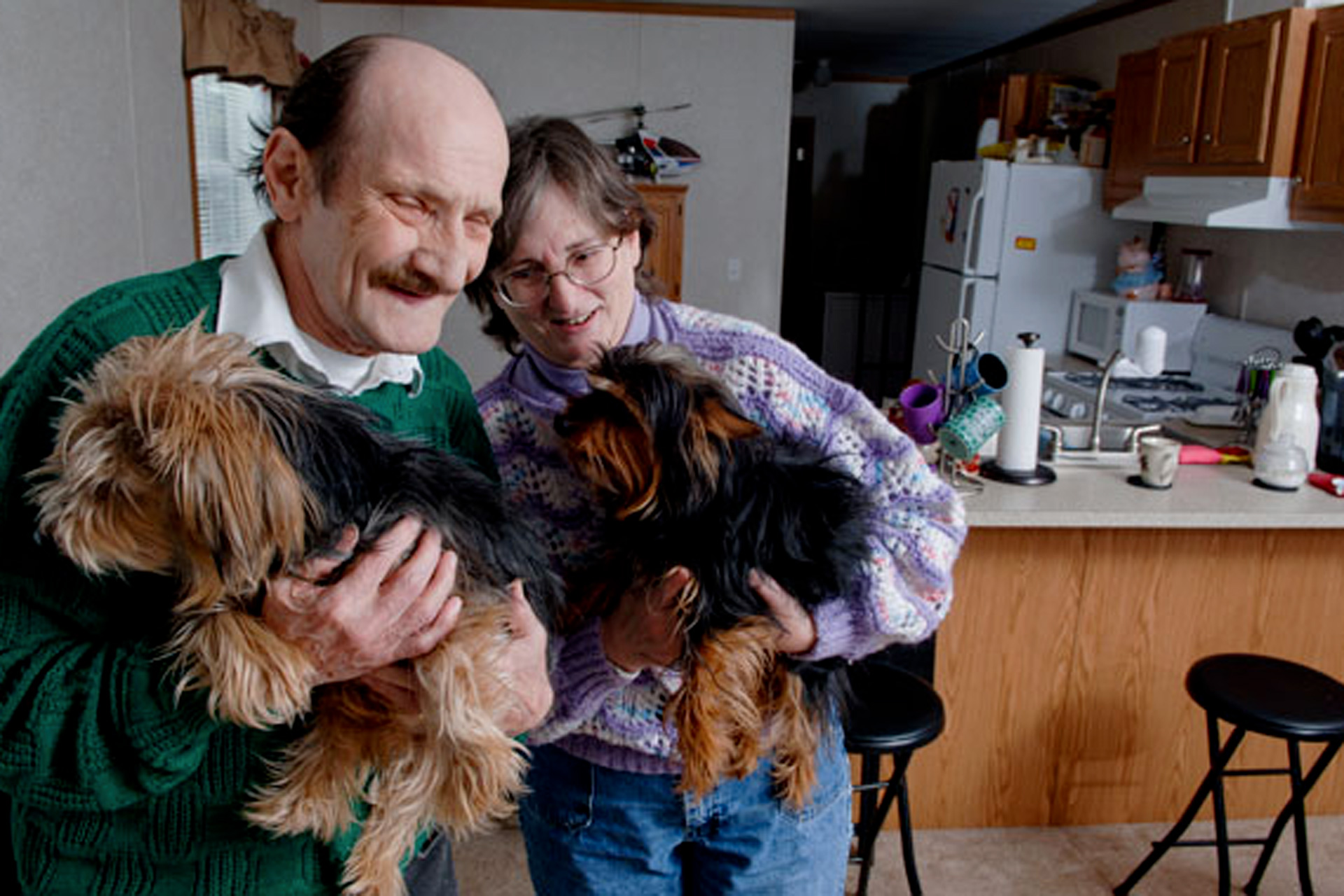Man and woman holding squirmy dogs in their kitchen