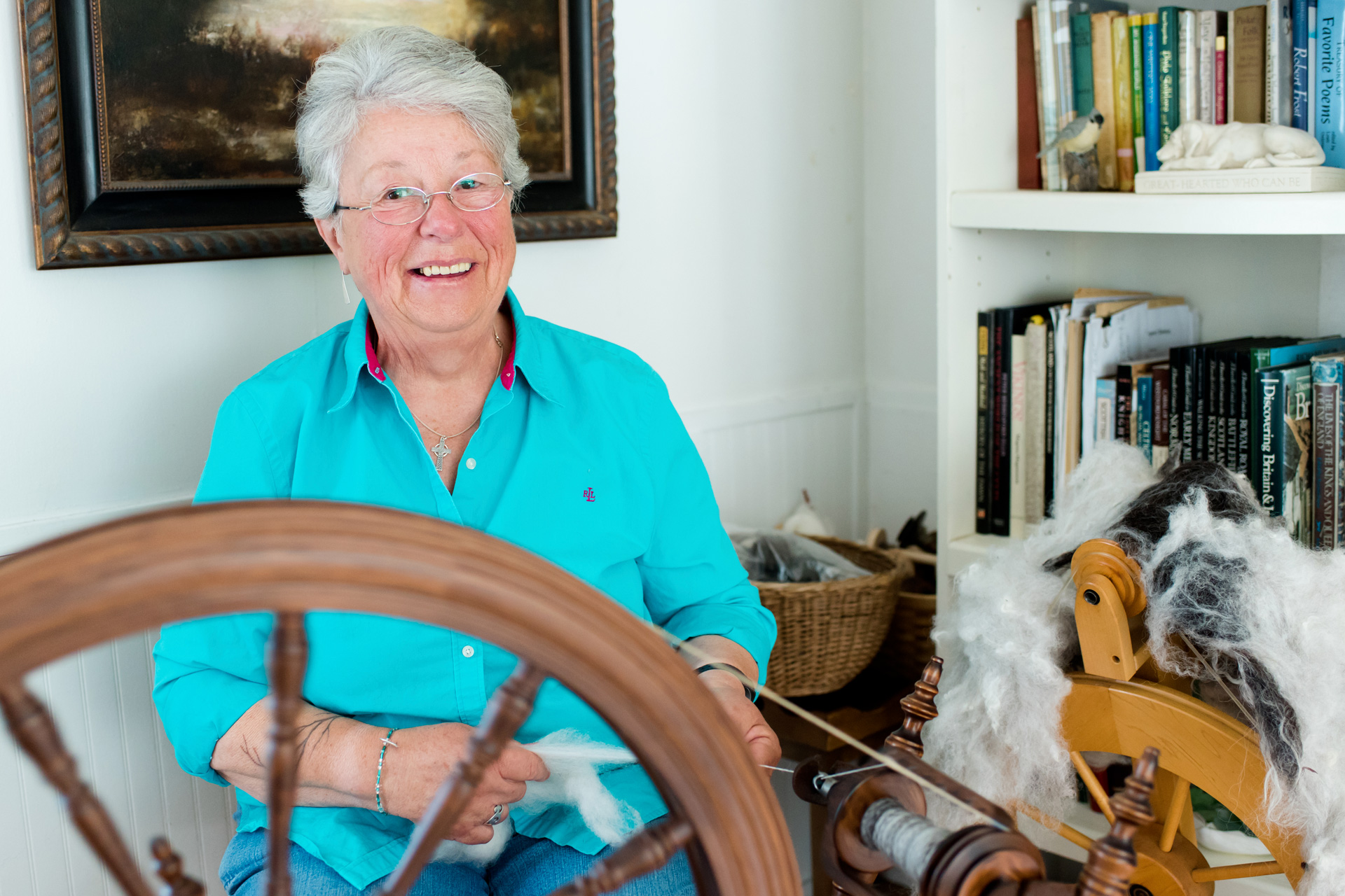 White-haired woman sspinning wool in her living room