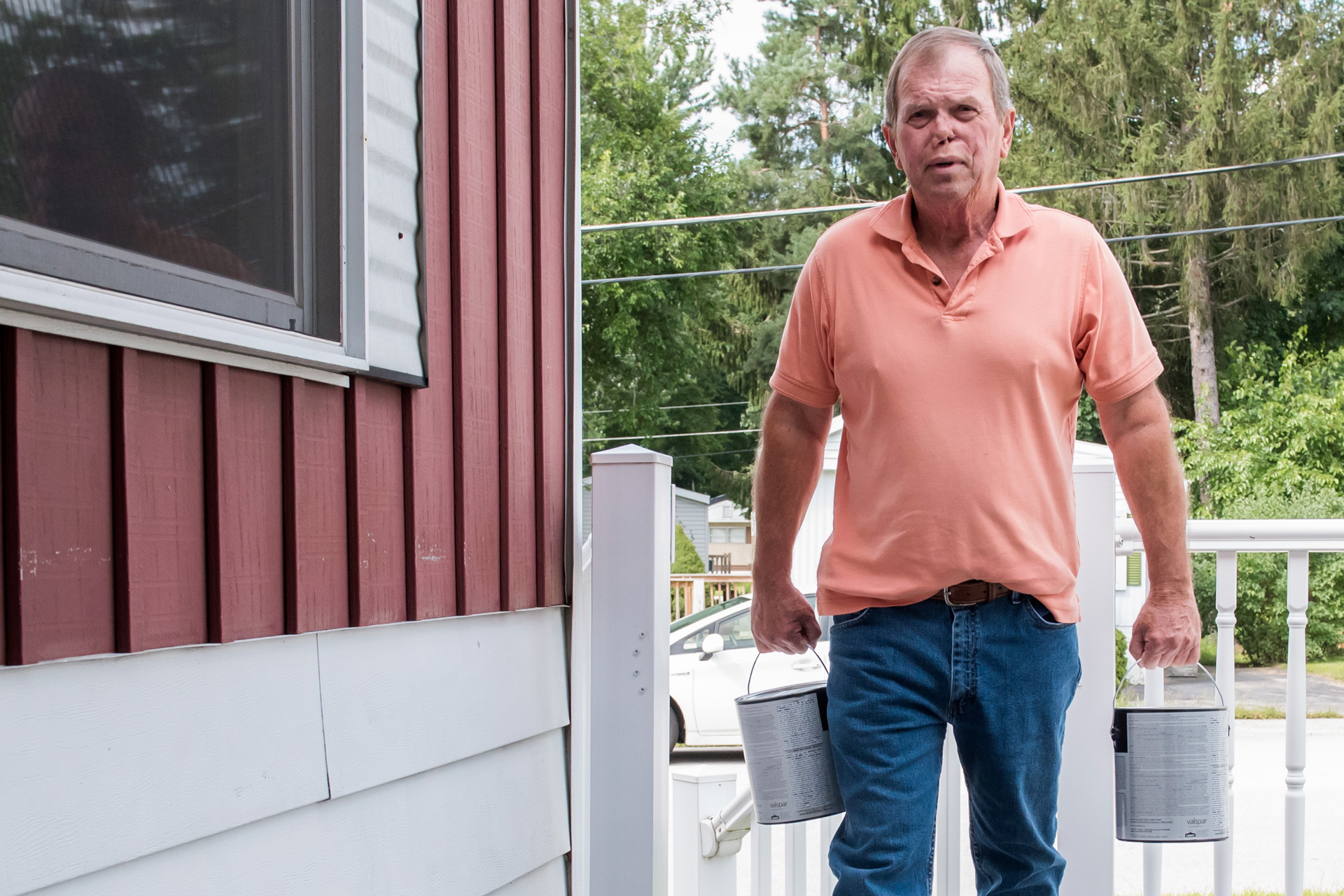 Man carrying two cans of paint onto porch