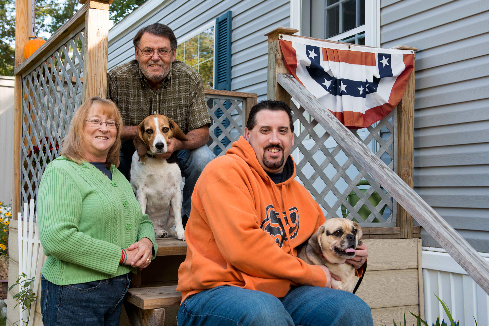 Two men, a woman and two dogs pose on steps to a manufactured home.