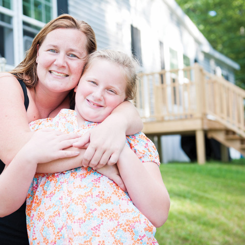 Mom hugging daughter in front of manufactured home