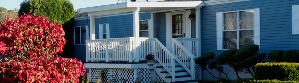 porch on side of blue mobile home