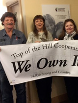 Board members of Top of the Hill Cooperative celebrate the purchase of their park with a banner saying We Own It