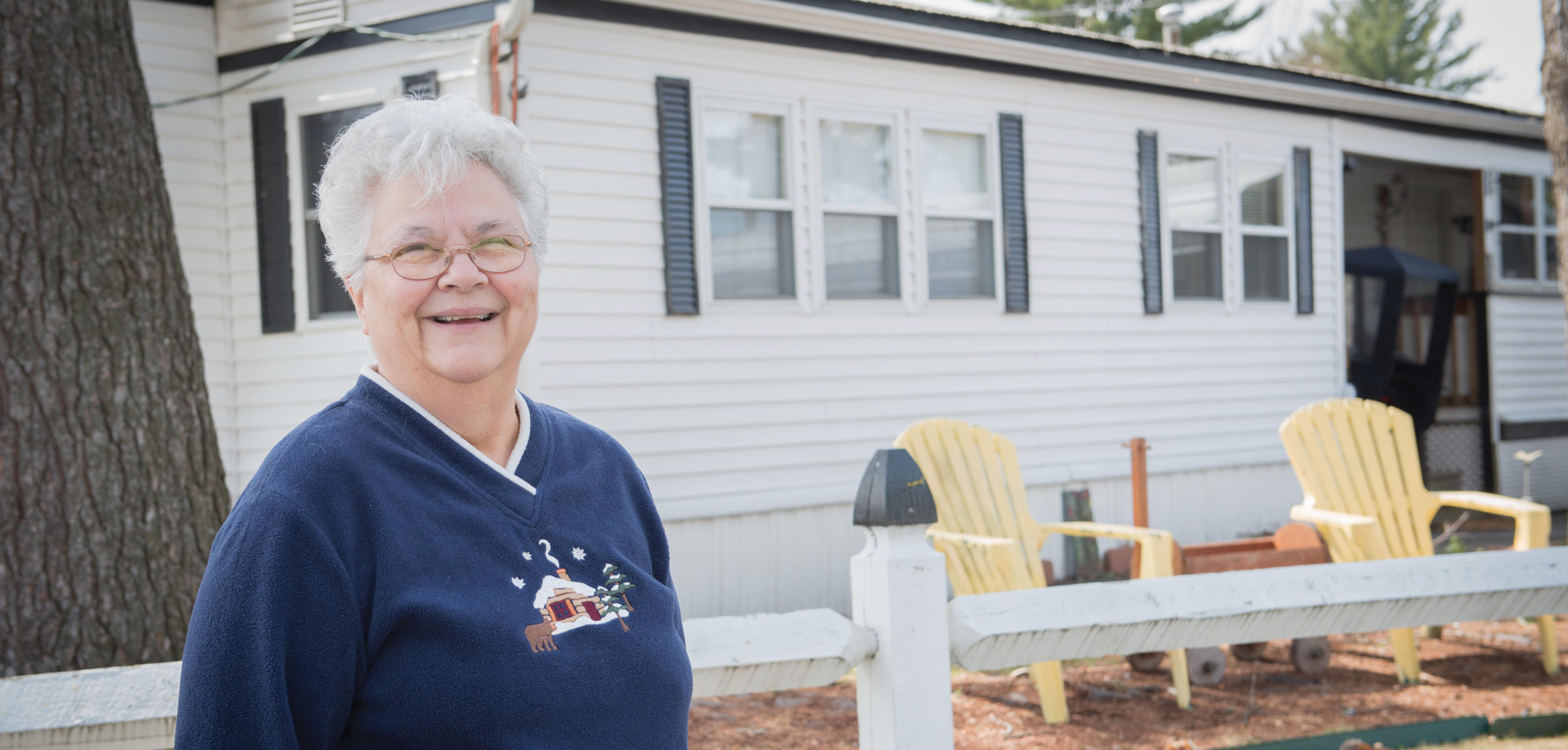 smiling woman in front of fence and house