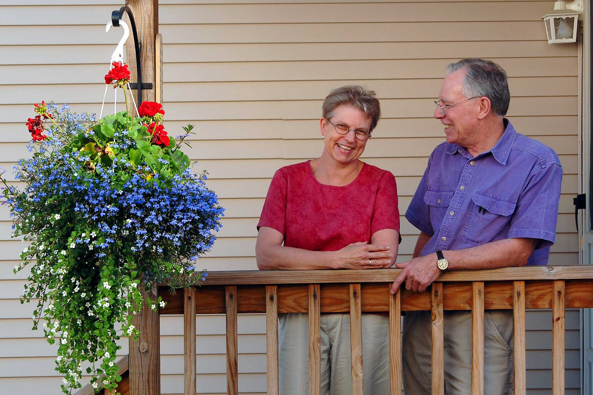 Middle-age couple stands on porch next to flower basket