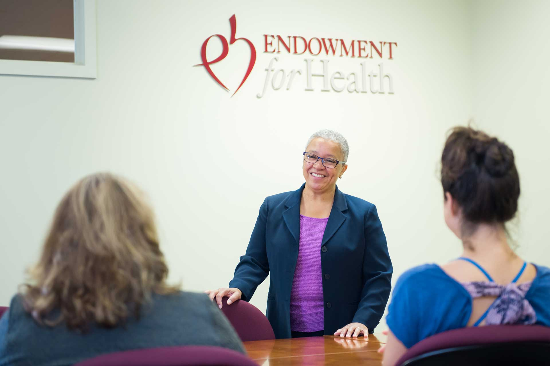 woman stands in conference room under Endowment for Health Logo on wall