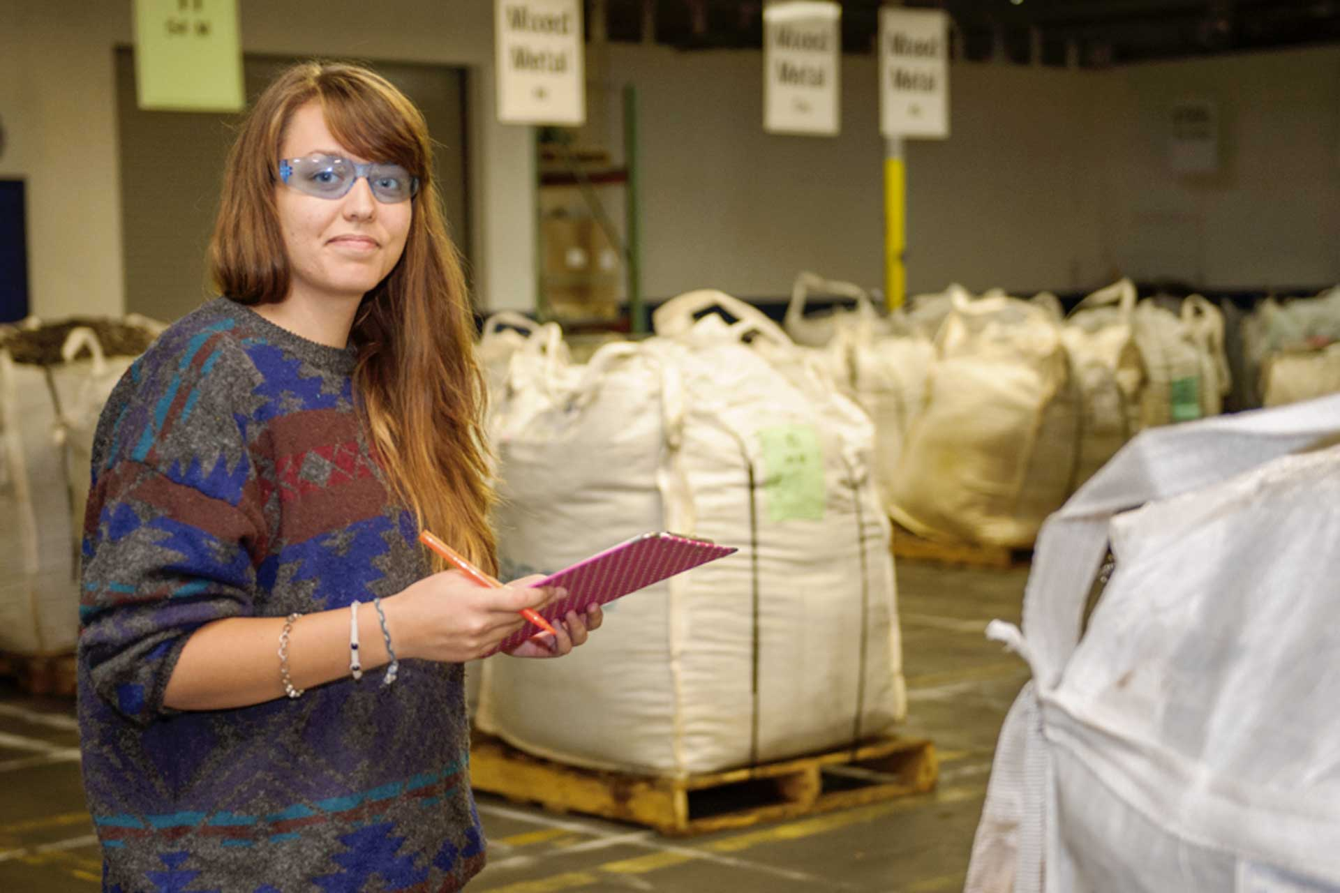 Young woman with safety glasses and a clipboard checks inventory