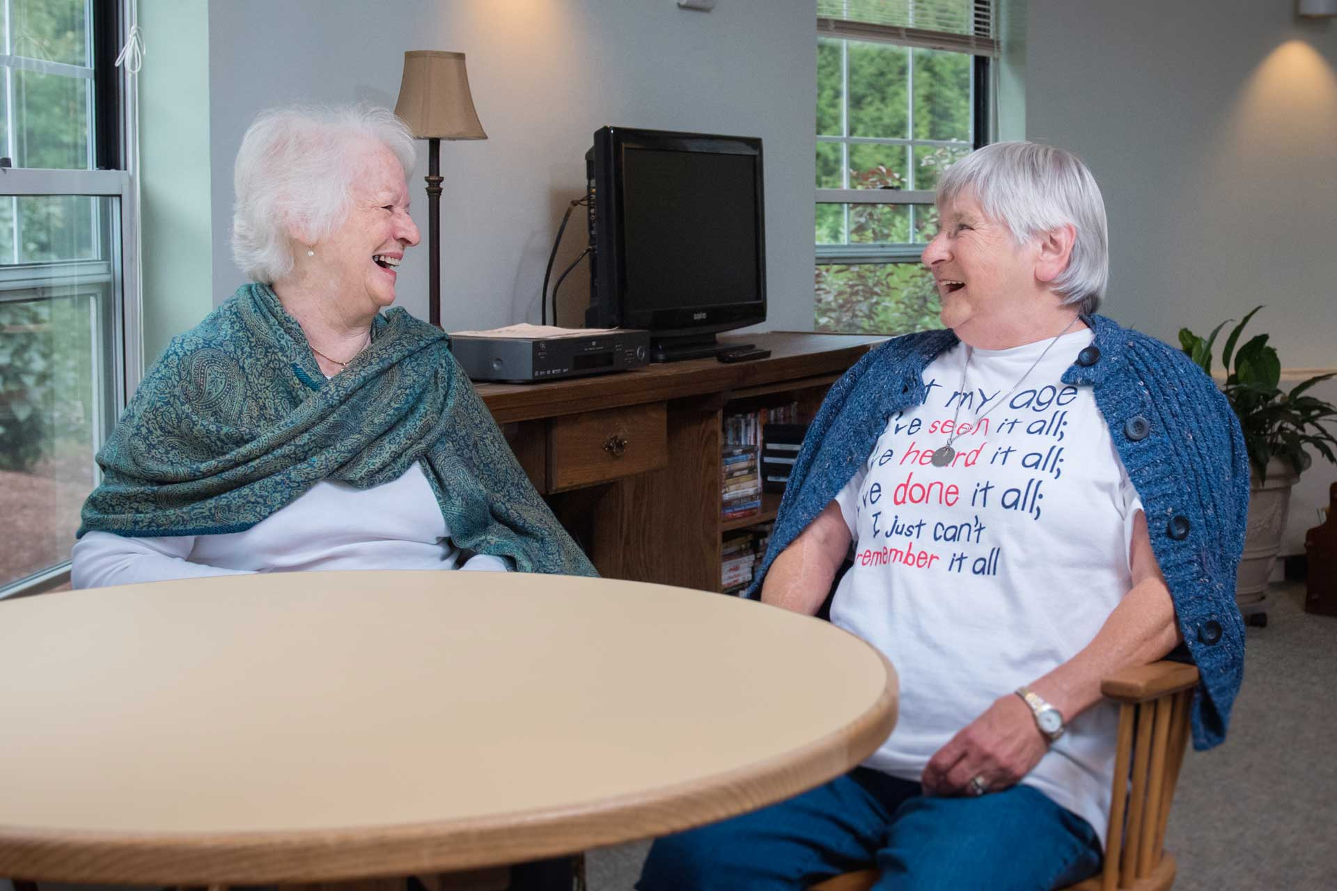 Two woman share a laugh at a table