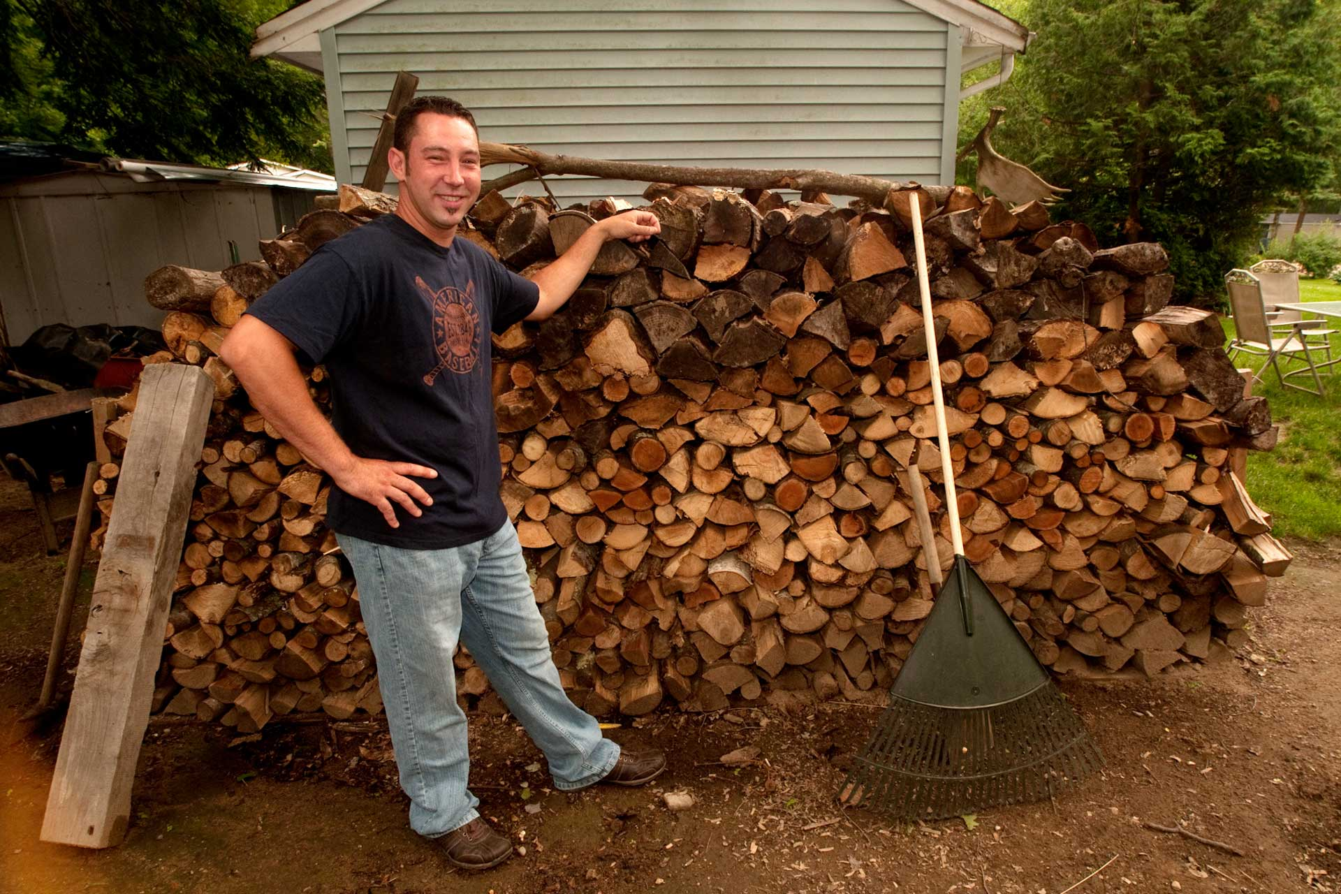 Man standing beside a neatly-stacked woodpile
