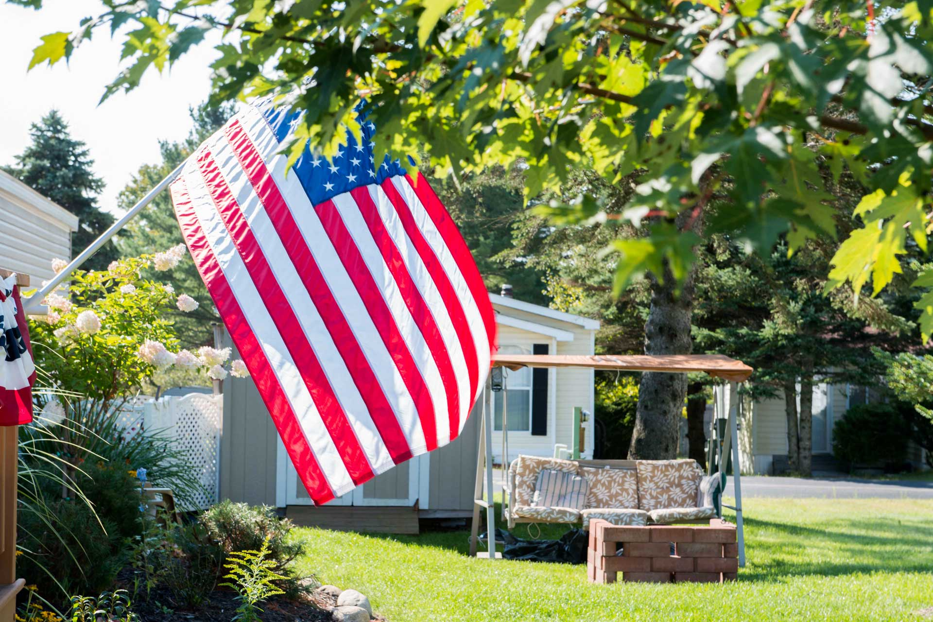 Attractive yard in a resodent-owned community with U.S. flag in foreground
