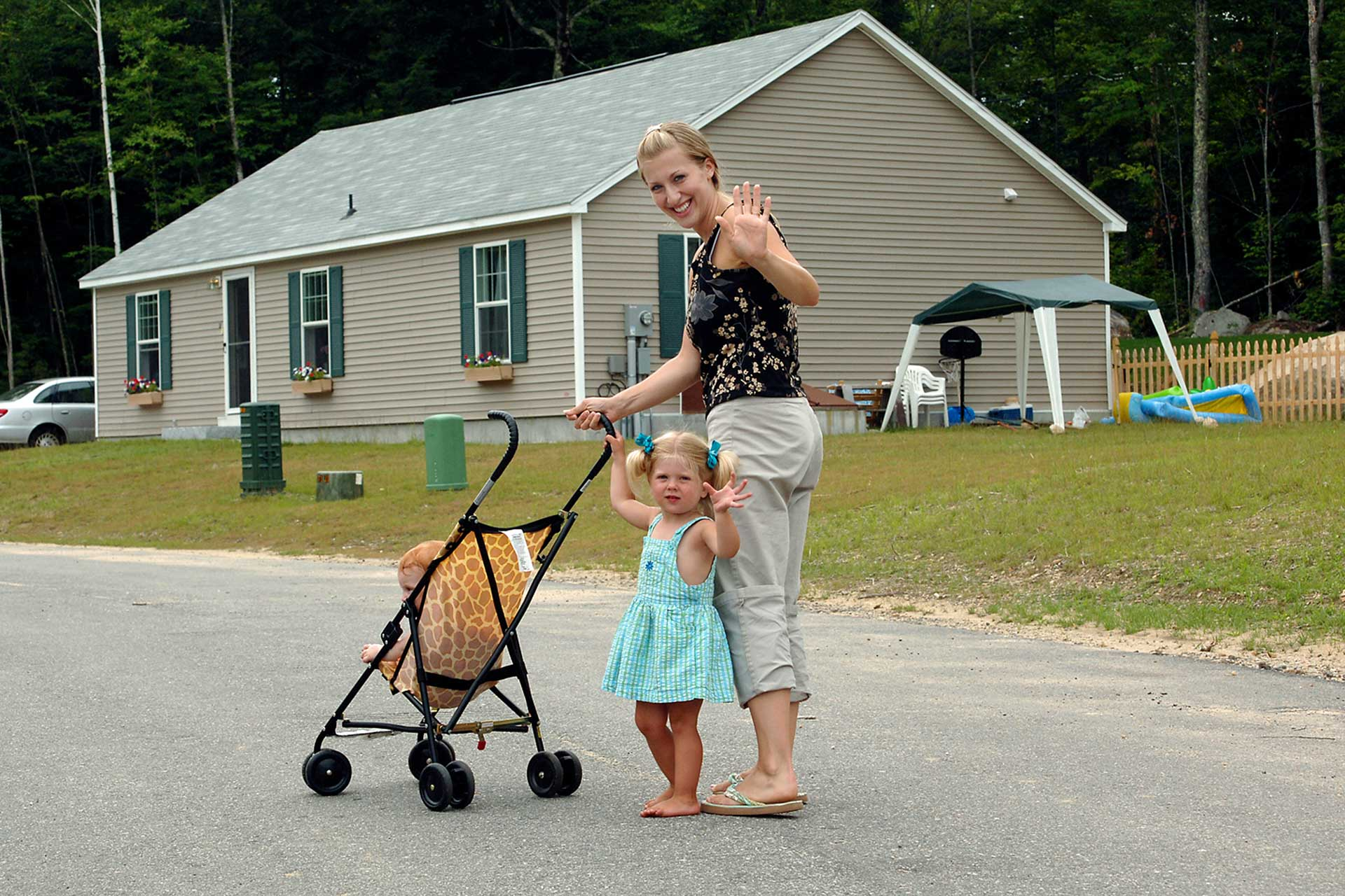 Mom and daughter turn to wave while pushing a stroller down the street
