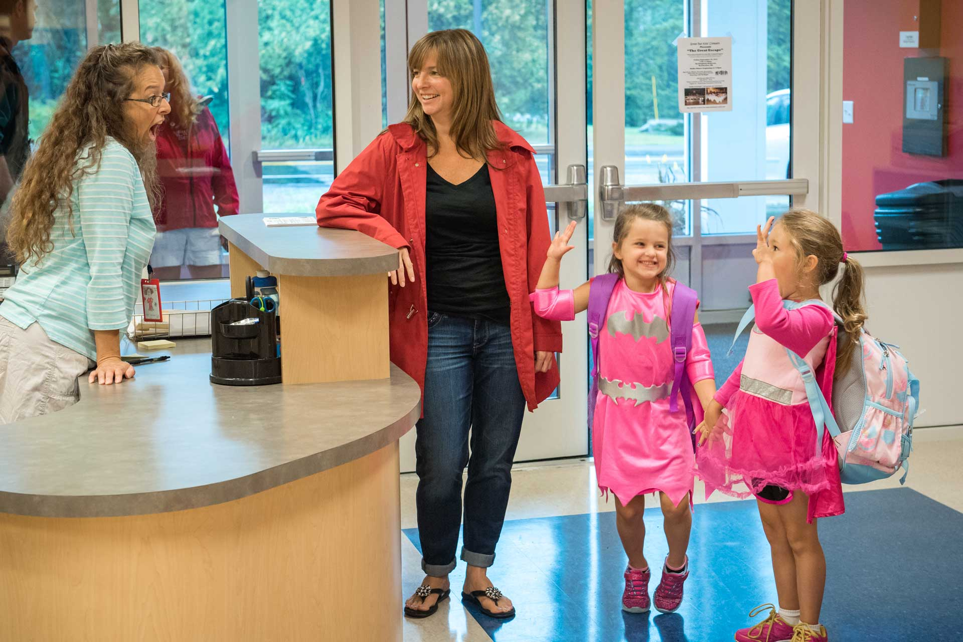 two girls say hi to receptionist with mom leaning on counter