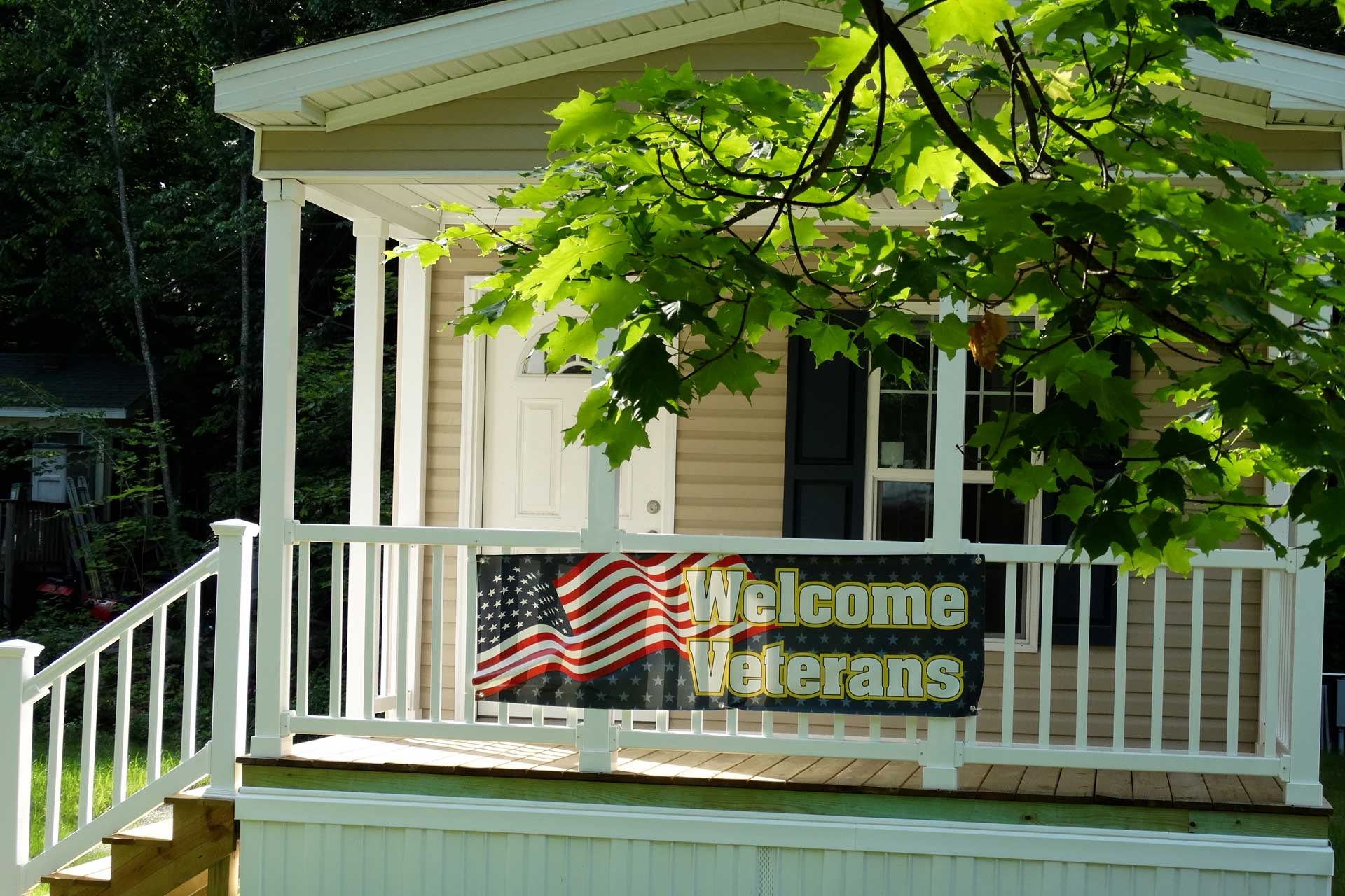 Sign saying Welcome Veterans hands from the railing of a porch.