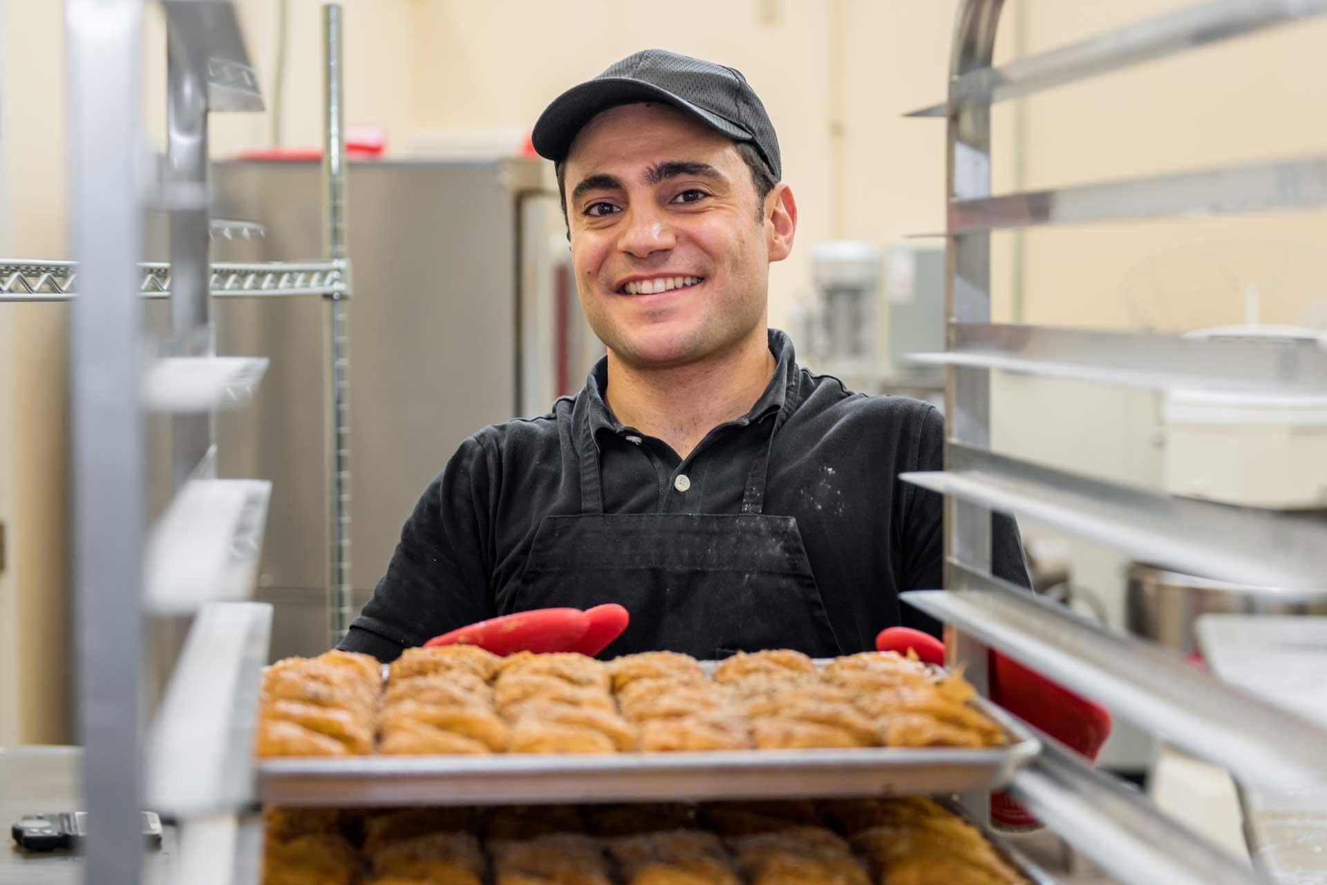 Baker putting a sheet of baklava on rack